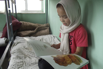 Afghan girl reading The Lion Who Saw Himself in the Water