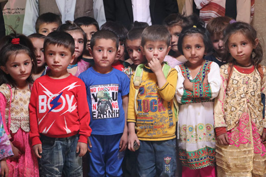 Shughni kids wearing colorful clothes with their teachers in the background
